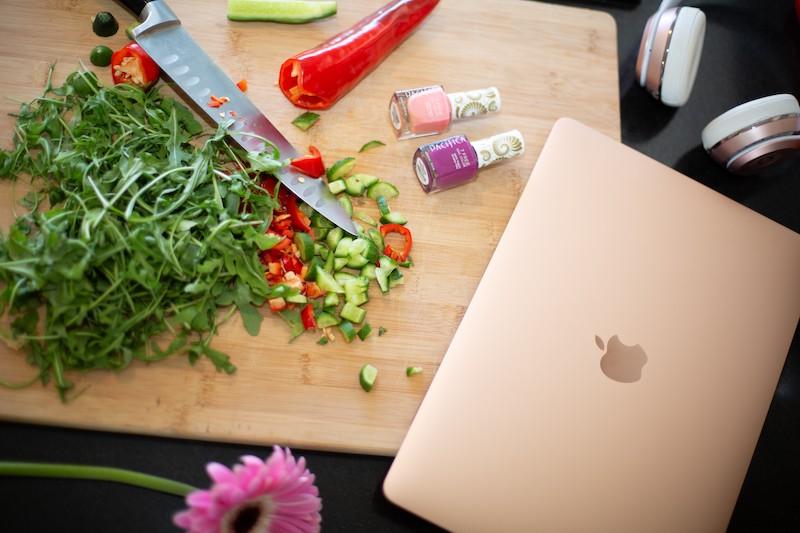 בלגאן על קרש מטבח - ירקות חתוכים, וליד זה פלפל אדום, 2 בקבוקי לק, פרח, מחשב וסכין