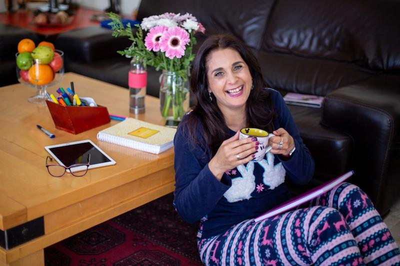 איילת יושבת על השטיח, נשענת על השולחן, על הברכים מחברת, ומחזיקה כוס תה ביד ןמחייכת מול המצלמה. על השולחן מאחרו יש מחברת צהובה, פרחים, אייפד