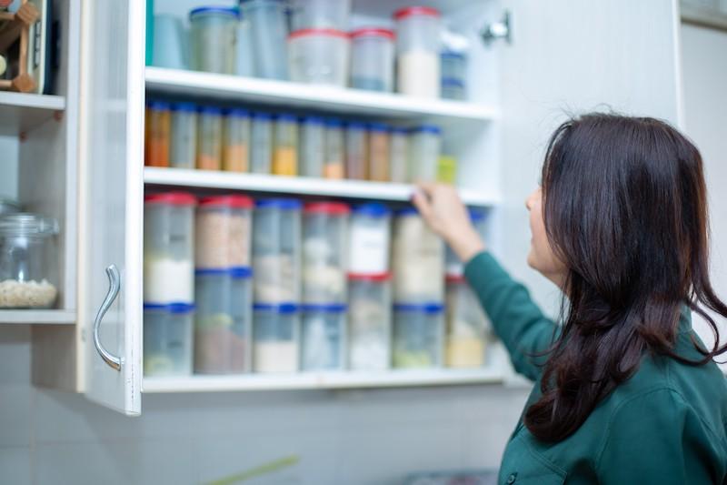 איילת עומדת מול ארון במטבח, הדלתות פתוחות, ויש קופסאות מאורגנות ומסודרות אחת ליד השנייה. איילת עם חולצה ירוקה ורואים רק את הגב שלה