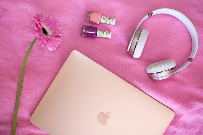 על שמיכה ורודה מונחלים מחשב של אפל בצבע ורוד זהב, ראוזניות, 2 לקים, אחד ורוד ואחד סגול, ופרח