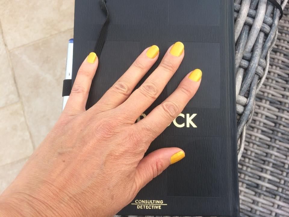 היד של איילת, עם הלק הצהוב, מונחת על יומן שחור