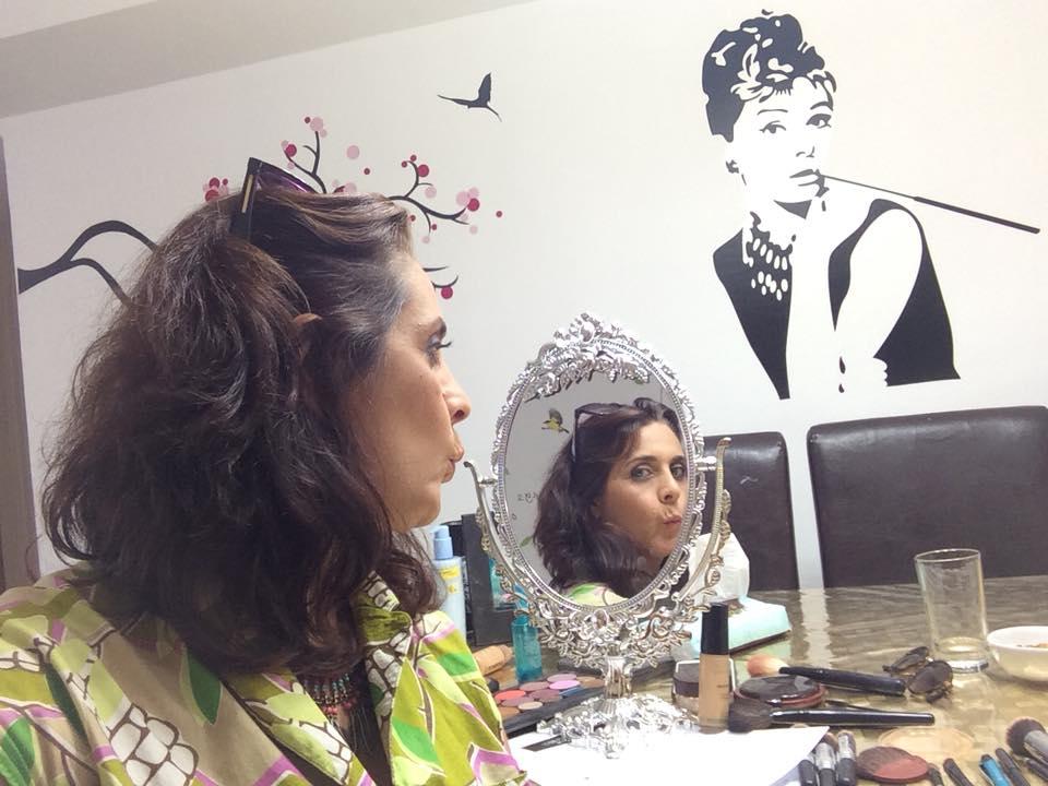 איילת מול מראה, נותנת לעצמה נשיקה במראה. שמלה ירוקה. ממול על הקיר תמונת קיר של אישה משנות ה-50