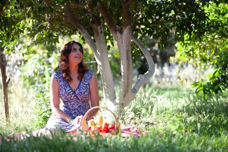 איילת יושבת על הדשא, עם סלסלת ירקות לפניה, שמלה כחולה ומסתכלת לשמיים