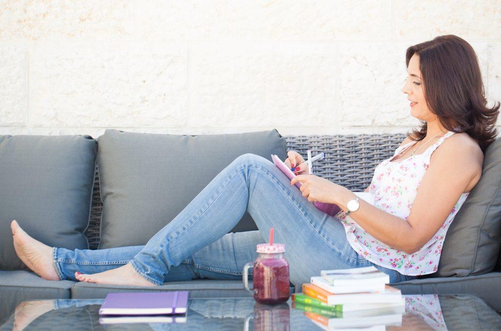 פרופיל - איילת יושבת על ספה, רגליים על הספה, וכותבת סבתוך מחברת. על השולחן מקדימה שייק אדום וערימת ספרים