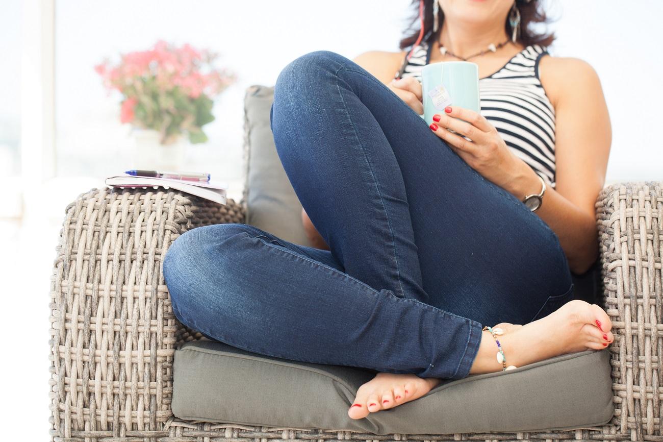 איילת יושבת עם רגליים מסוקלות על ספת קש, וכוס תה ביד