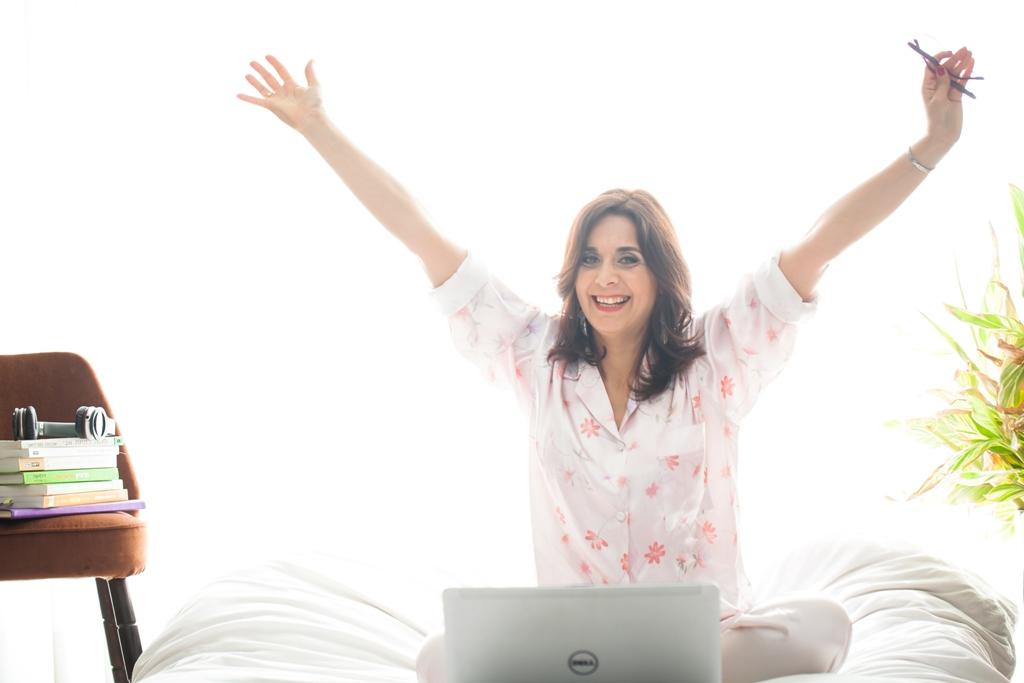 איילת עם פיג'מה ורודה, יושבת על מיטה עם סמיכה לבנה, ידיים למעלה לצדדים, מחייכת, ויש מחשב על המיטה