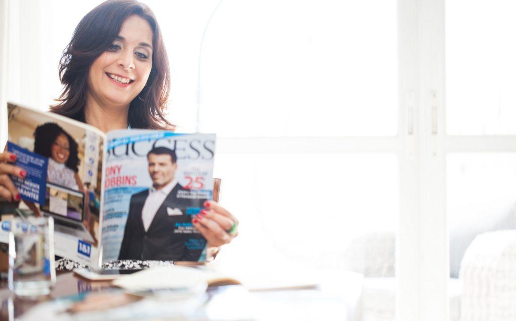 איילת מחזיקה וקוראת מגזין של success , ומחייכת