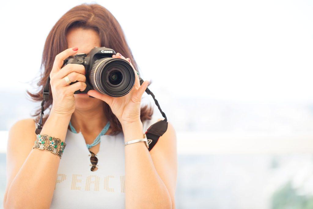 איילת מסתכלת דרך עדשת מצלמה ומצלמת. לובשת חולצה תכלת, וצמיד ירוק דביד