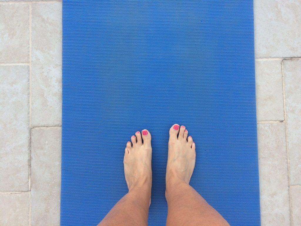 רגלים עומדות על מזרון יוגה כחול