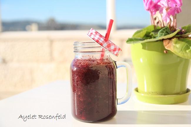 כוס צנצנת עם שייק אדום. קשית אדומה בתוך הכוס, והמכסה תלוי על הקשית. ברקע עציץ ירוק עם פרח ורוד ושמיים כחולים