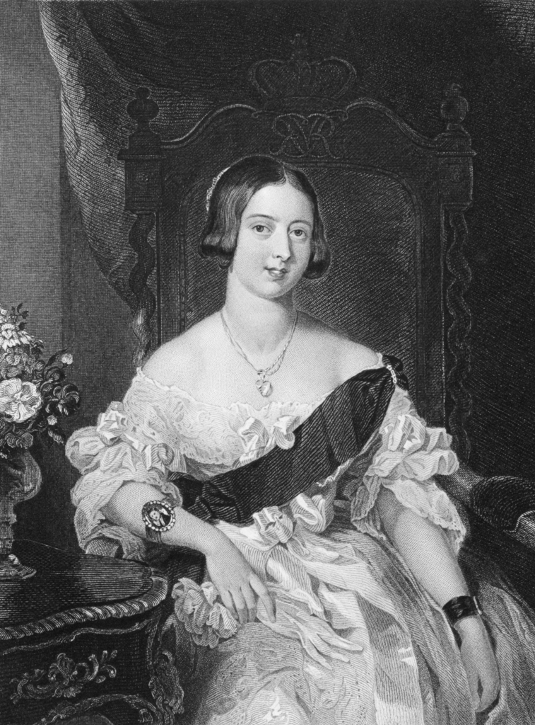 המלכה ויקטוריה, יושבת על כס המלכות, שמלה לבנה עם סרט שחור שחוצה אותה מהכתף הימנית למותן שמאל, נשענת עם המרפק על שולחן מעוצב שיש עליו גם אגרטל עם פרחים. תמונה בשחור לבן