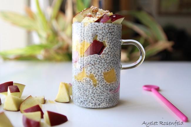 פודינג צ'יה בכוס זכוכית שקופה עם ידית קטנה, מעורבב עם פירות, ומעל חופן של תפוחים ואגוזים.הכוס עומדת על שולחן לבן ויש תפוחים חתוכים וכפית ורודה על השולחן