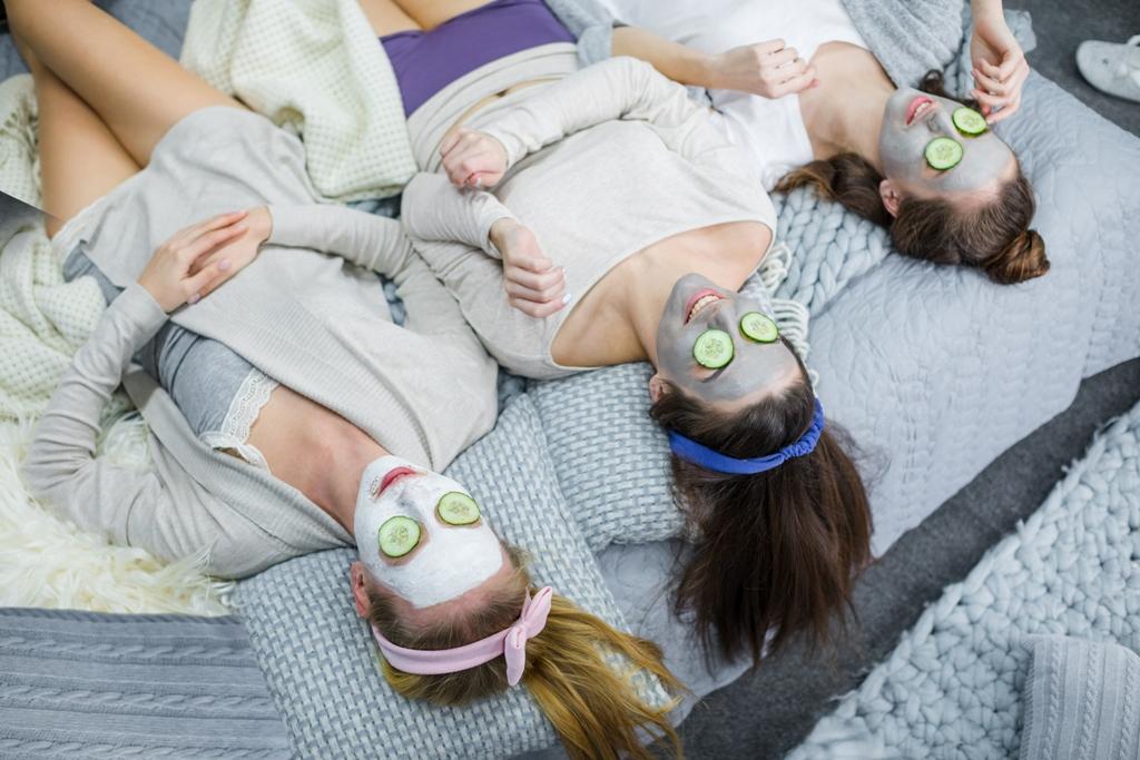3 נשים שוכבות על הגב במיטה, עם סרטים על השיער ומסיכות קוסמטיות על הפנים, ופלחי מלפפון על העיניים ונהנות מרגע של שלווה וטיפוח עצמי