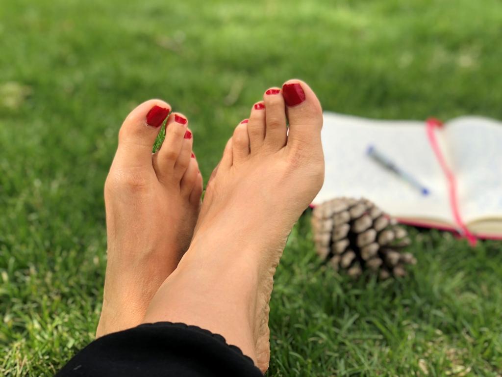 רגליים של אשה עם לק אדום בציפורניים וברקע מחברת פתוחה, עט ואיצטרובל