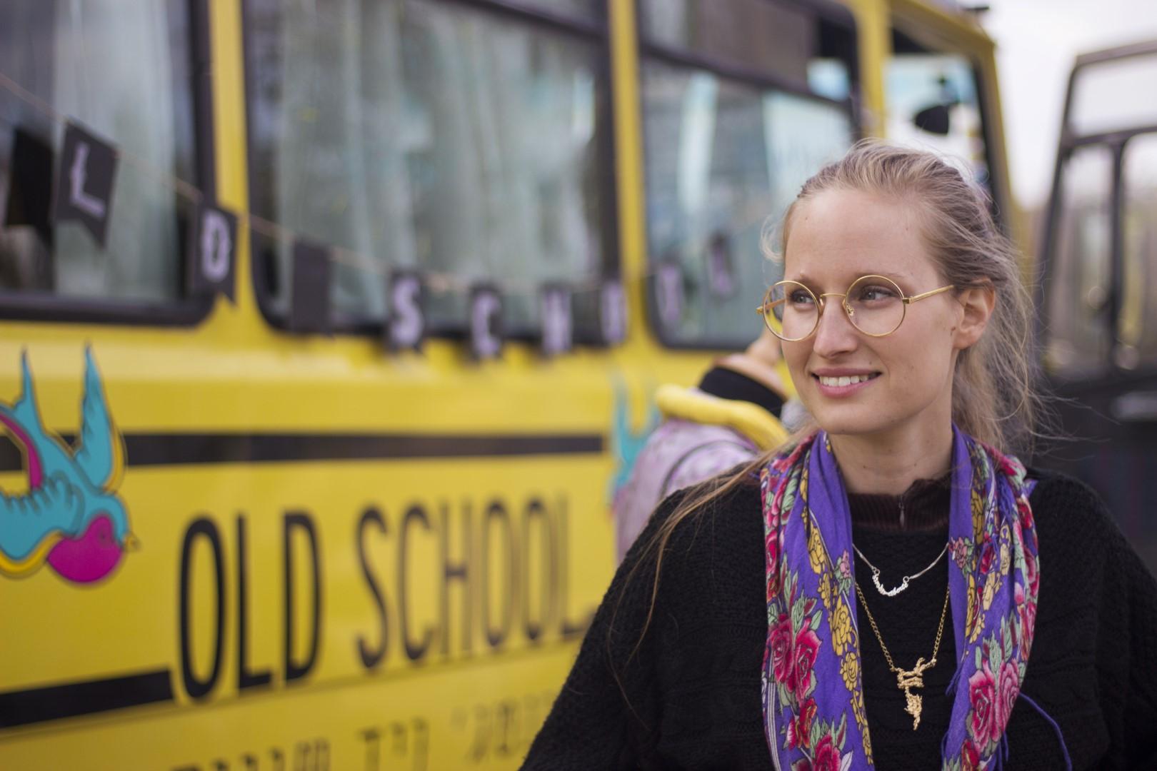 נוגה סדן עומדת ליד האוטובוס הצהוב שלה, שכתוב עליו old school