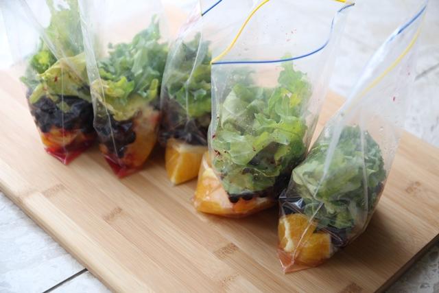 5 שקיות עומדות עם כל הרכיבים לשייק - תפוז, עלים ירוקים, פירות יער