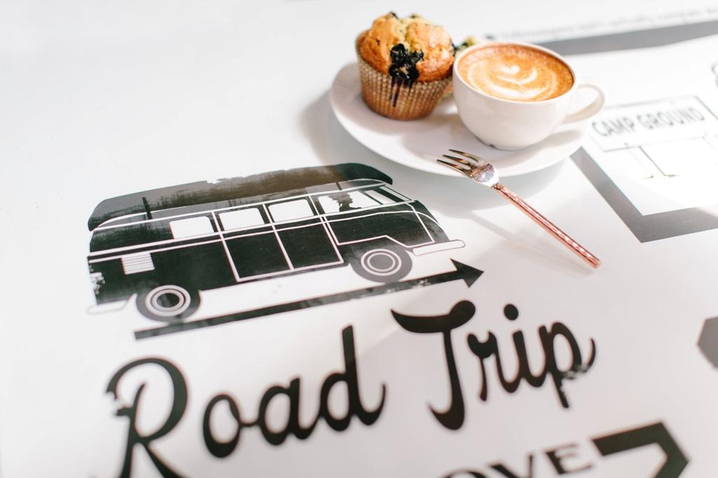 ציור של אוטובוס בצבע שחור ומתחת כתוב road trip ובצד צלחת עם עוגת מאפין וכוס קפה