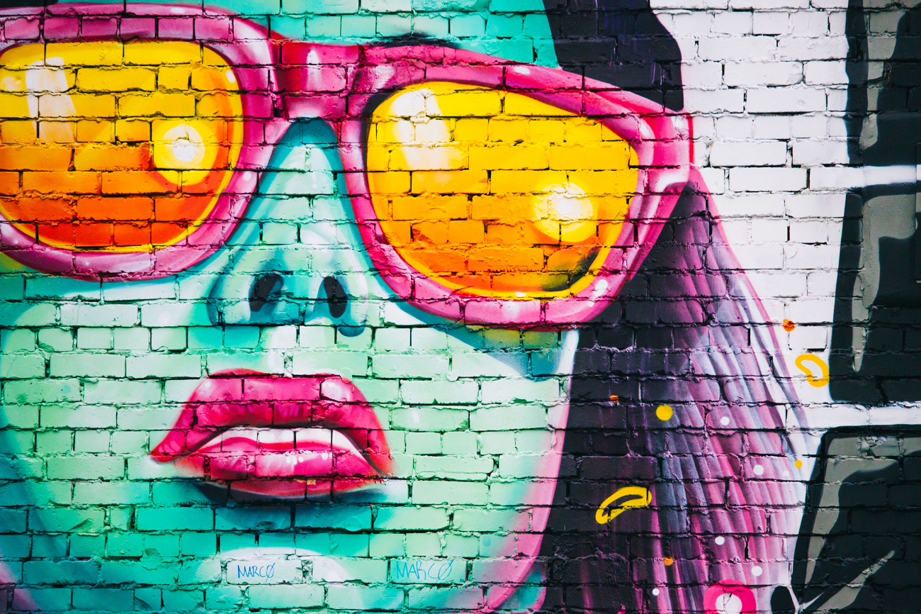 ציור קיר של אישה עם משקפיים כתומות-ורודות וליפסטיק ורוד. הפנים שלה כחולות