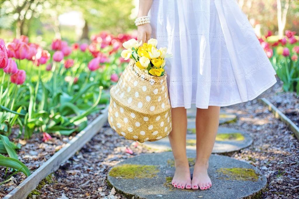 אישה עם שמלה לבנה, רואית רק מהחלק של הבטן ומטה, יחפה, עם לק אדום בציפורניים ברגליים, עומדת על אבן בגינה, וביד סל קש עם פרחים צהובים
