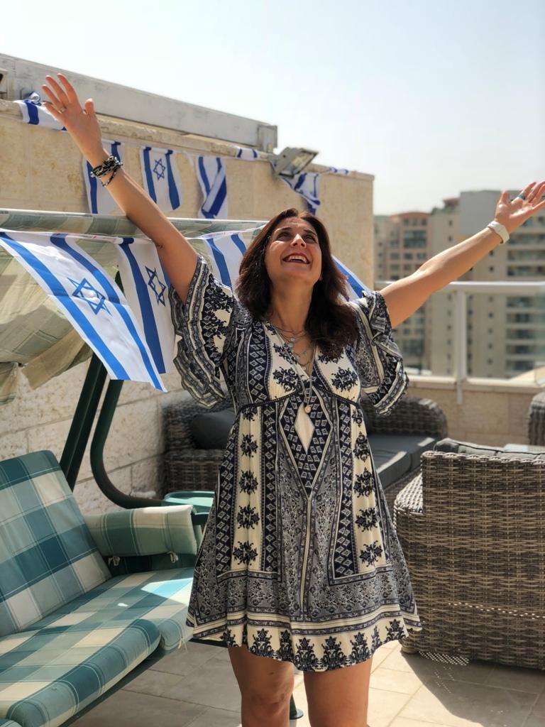 איילת עומדת עם ידיים למעלה שמחה, עם שמלה כחול לבן, וברקע מתנפנפים דגלי ארץ ישראל